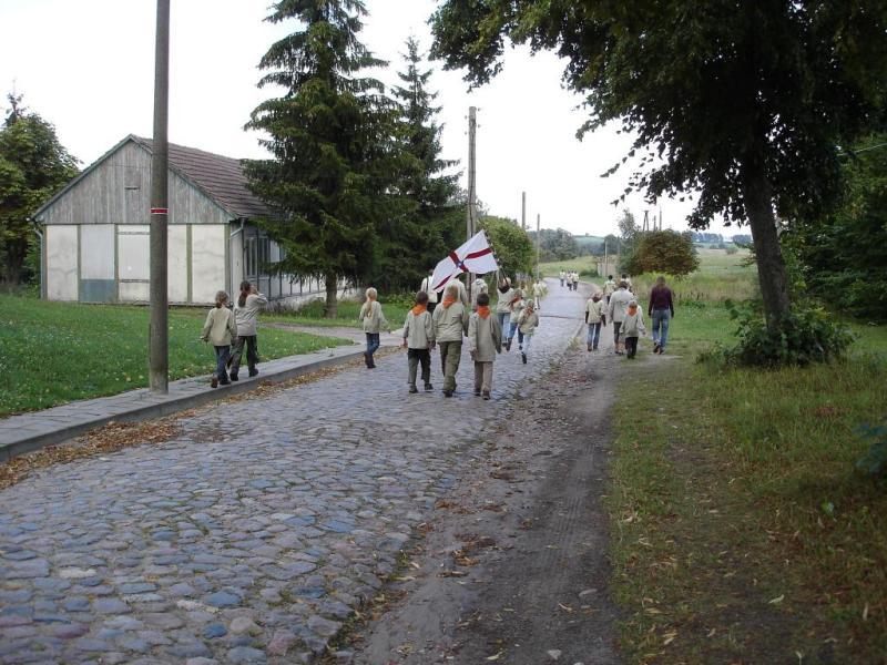 Mit dem Banner geht es durch das Dorf zur Kirche.